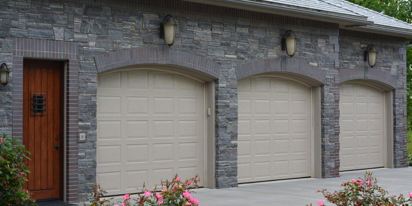3 bay garage with 3 tan garage doors