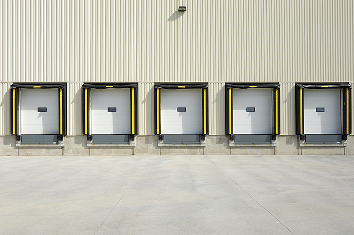 Warehouse Loading Dock with 5 white garage doors and other loading dock equipment surrounding them
